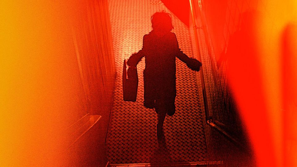 Rot-Orangefarbenes verschwommenes Bild mit den Umrissen einer Frau