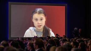 Klimaaktivistin Greta Thunberg ist auf einer Leinwand zu sehen, davor ist schemenhaft Publikum zu erkennen