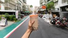 Eine Hand hält einen Plastikbecher mit Bubble Tea
