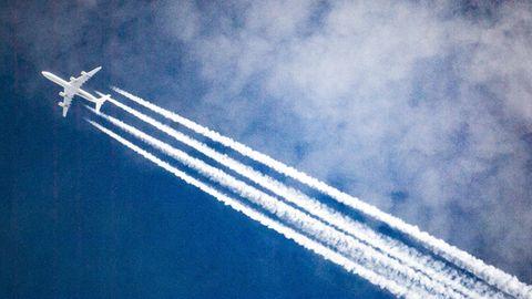 Ein Flugzeug zieht Kondensstreifen hinter sich her, während es durch die Wolken fliegt