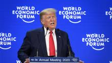 """Vor einer blauen Wand mit weißem """"World Economic Forum"""" steht US-Präsident Donald Trump am Rednerpult"""