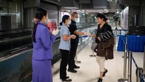 Passagiere erhalten Flugblätter zum Coronavirus am Flughafen in Bangkok
