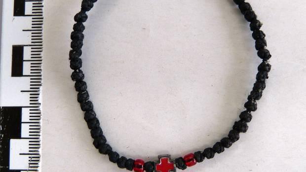 Das Foto zeigt ein schwarzes Armband mit rotem Kreuz