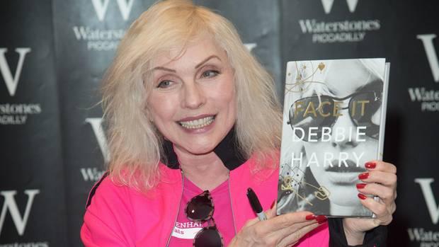 Debbie Harry hält ihre Autobiografie in die Kamera und lächelt
