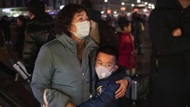 Coronavirus in China: Eine Frau und ein Junge tragen Atemmasken zum Schutz vor dem Virus