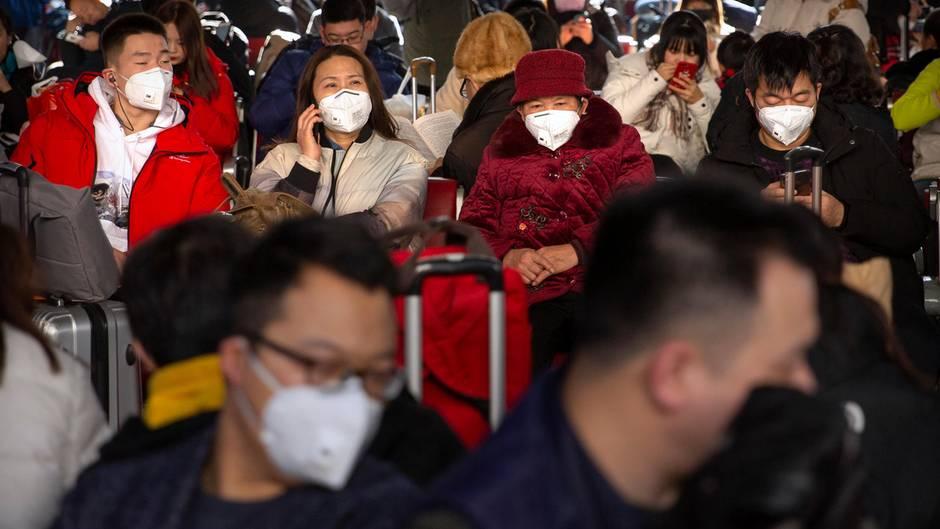 Reisende tragen als Schutzmaßnahme gegen die Verbreitung des Coronavirus Mundschutz