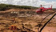 29.01.2019, Brasilien, Brumadinho: Feuerwehrleute bergen mit Hilfe eines Hubschraubers eine Leiche
