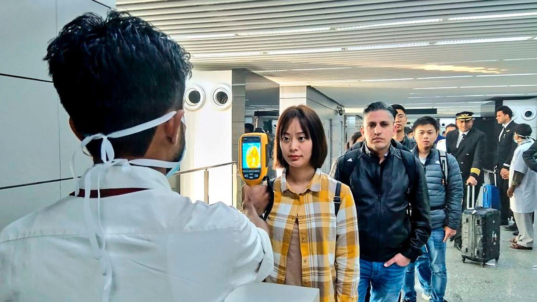 Coronavirus: Ein Flughafenmitarbeiter untersucht Reisende, die aus China und Hongkong ankommen
