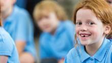Kinder in blauen Schuluniformen in einer Klasse