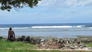 Ein Junge sitzt am Meer. Neben ihm liegt Plastikmüll