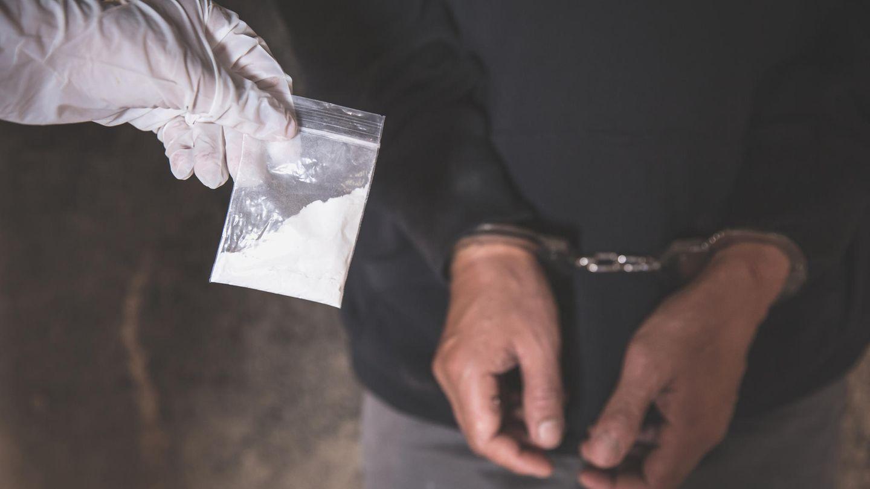 Ein Drogendealer wird verhaftet und trägt Handschellen. Eine Hand im Handschuh hält eine Tüte mit weißem Pulver hoch.