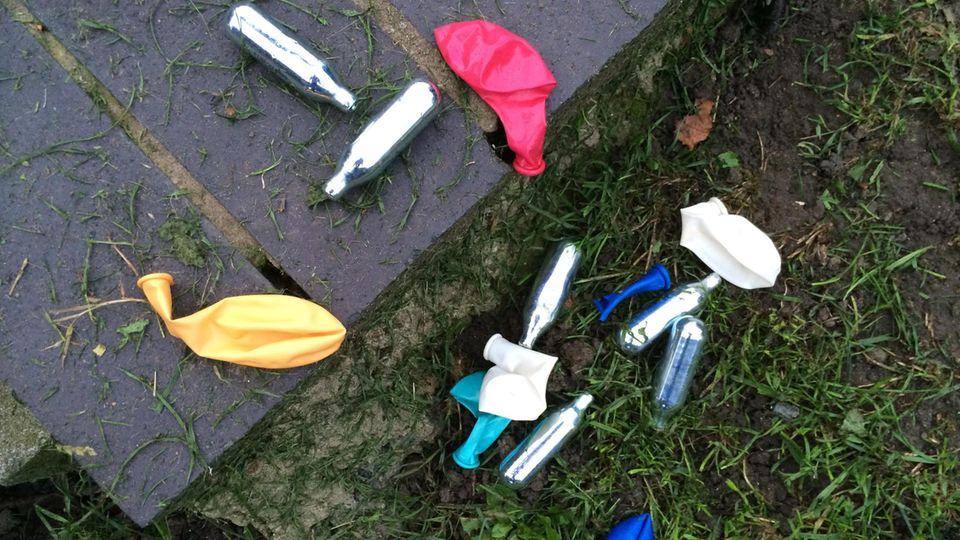 Lachgas-Kartuschen und Luftballons liegen auf dem Boden