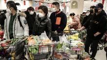 Chinesische Männer und Frauen schieben mit Masken vor dem Mund volle Einkaufswagen mit Lebensmitteln durch einen Supermarkt