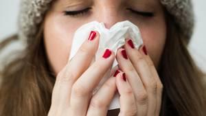 Grippe 2020: Eine Frau benutzt ein Taschentuch