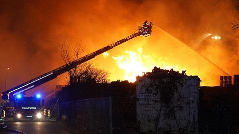 Ilsfeld: Feuerwehrleute versuchen Stapel von brennenden Holzpaletten zu löschen