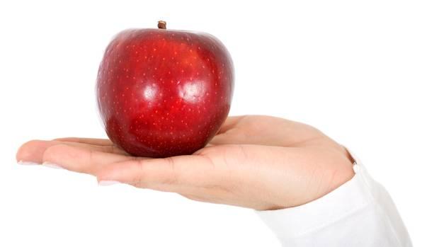 Diäten im stern-Check: Frau hält roten Apfel in der Hand