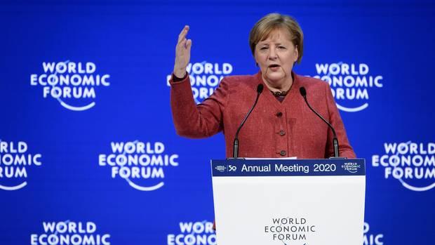 """Bundeskanzlerin Merkel steht auf dem Podium vor einer blauen Wand mit """"World Economic Forum""""-Logo und gestikuliert"""