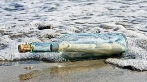 Eine durchsichtige Weinflasche mit einem aufgerollten Papier darin und einem Korken Treibt im Wellensaum