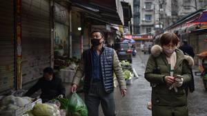 In einer Marktstraße in China gehen zwei Männer und tragen Atemmasken gegen das Coronavirus