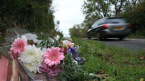 Ein Blumenstrauß mit rosa Gerbera und weißen Nelken liegt am Straßenrand, während ein graues Auto schnell vorbeifährt