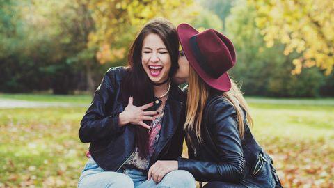 Zwei Freundinnen sitzen auf einer Wiese und tuscheln