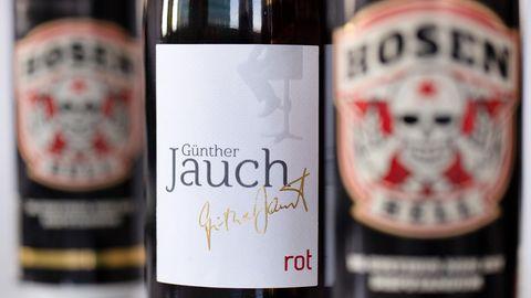 """Eine Flasche Wein """"Günther Jauch""""steht zwischen Bierdosen """"Hosen Hell"""" von der Band """"Die Toten Hosen"""". Beide Produkte werden in einem Discounter verkauft."""