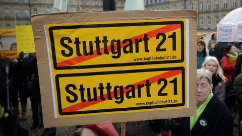 Eine Frau hält bei einer Demoim Jahre 2012 ein durchgestrichenes Stuttgart21-Plakat vor dem Finanzministerium im Neuen Schloss in Stuttgart in die Höhe