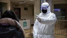 In der chinesischen Hauptstadt Peking weist ein Mitarbeiter im Sicherheitsanzug einen Fahrgast in einer U-Bahn-Station an