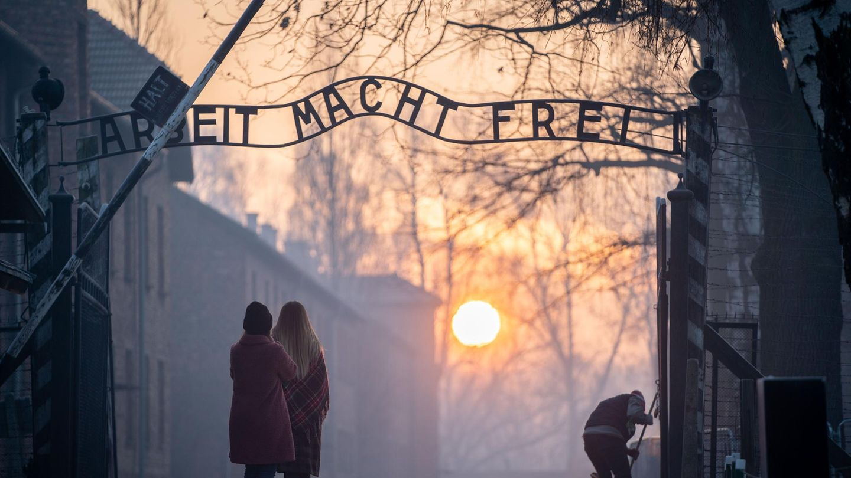 Besucher stehen am frühen Morgen am Tor zum früheren Konzentrationslager Auschwitz