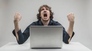 Verärgerter Mann vor einem Laptop