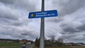 """Auf einem an einer Laterne befestigtem Schild im Ortsteil Gadheim ist """"Zukünftiger Mittelpunkt der EU"""" zu lesen"""
