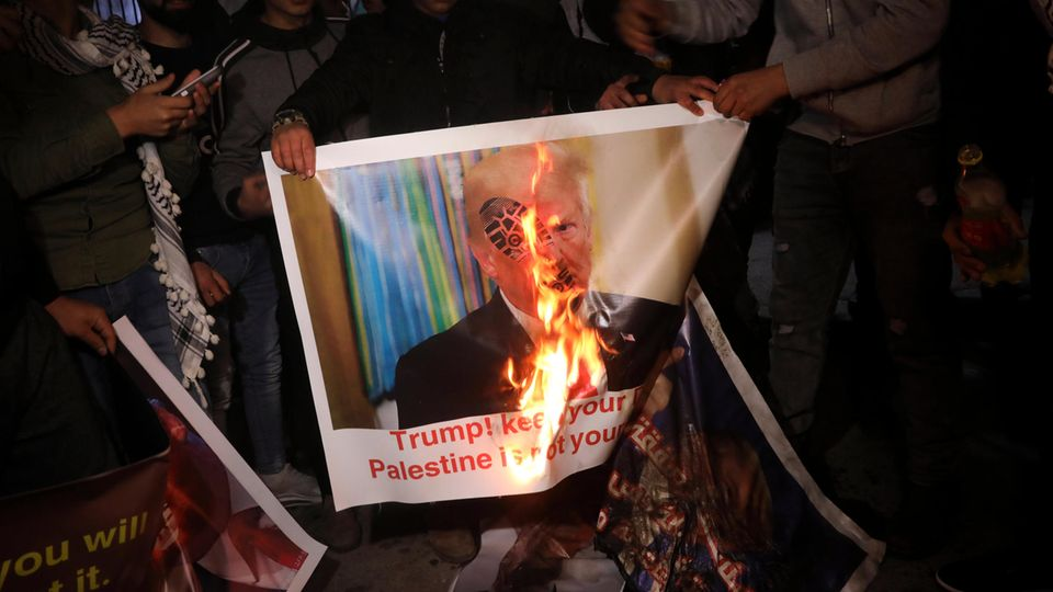 Demonstranten verbrennen ein Plakat mit dem Bild Donald Trumps