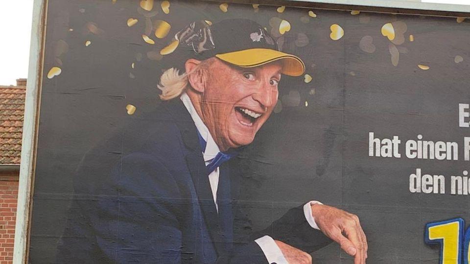 """Auf einem Werbeplakat ist links der Komiker Otto zu sehen und rechts der Slogan Essen hat einen Preis verdient: den niedrigsten"""""""