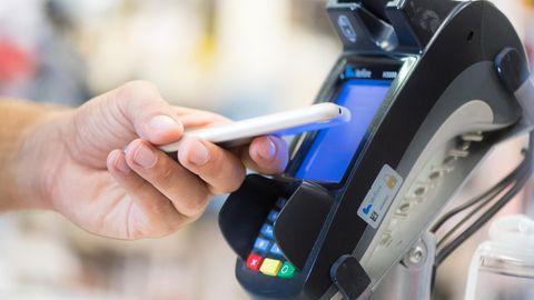 Ein Mann bezahlt in einem Laden in Berlin mit seinem Smartphone