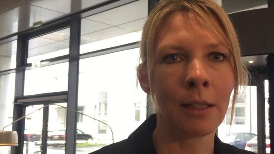 Eine blonde Frau mit schwarzem Blazer spricht in die Kamera. Im Hintergrund eine Glasfront mit Drehtür
