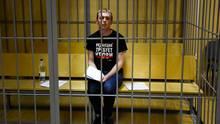 """Investigativ-Journalist Iwan Golunowsitzt vor Gericht in einer Zelle in Moskau. Auf seinem T-Shirt steht """"Die Redaktionfordert Blut"""". Vor einem halben Jahr wurde er freigelassen."""