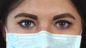 Eine Frau mit Mundschutz aus grünem Zellstoff schaut frontal in die Kamera. Sie hat braune Augen und braune lange Haare