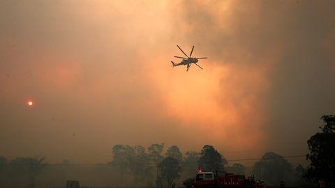 Ein Hubschrauber wirft Wasser auf ein außer Kontrolle geratenes Feuer