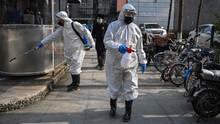 Auf den Straßen von Wuhan versprühen zwei Menschen Desinfektionsmittel