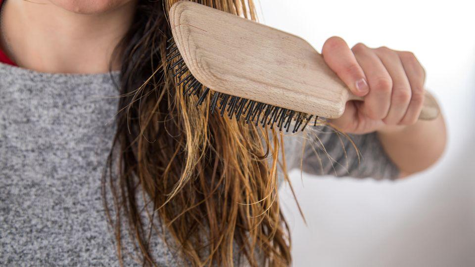 Fettige Haare: Frau kämmt sich mit einer Bürste ihre langen Haare