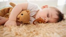 Ein Baby liegt schlafend auf einem Schaffell