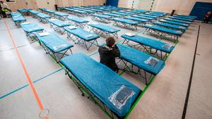 Dutzende Feldbetten stehen in einer Turnhalle auf dem Gelände des Flughafens in Frankfurt bereit