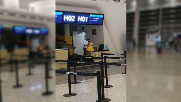 Ein Mitarbeiter in Schutzkleidung am Flughafen Wuhan