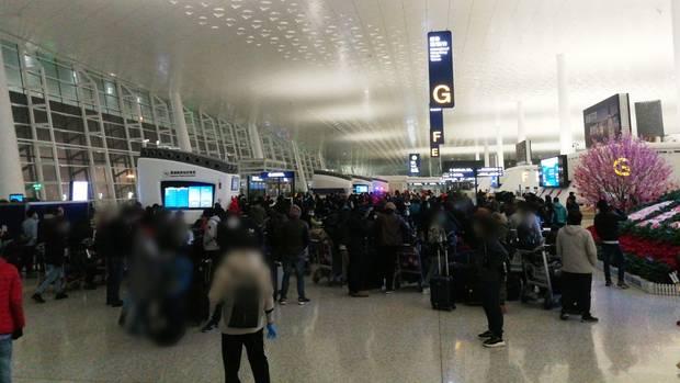Menschen warten am Flughafen Wuhan