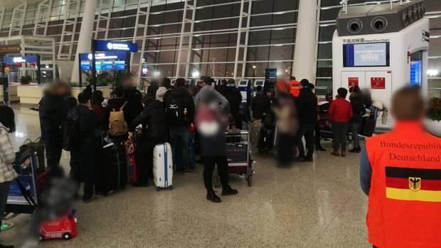 Menschen warten am Flughafen von Wuhan