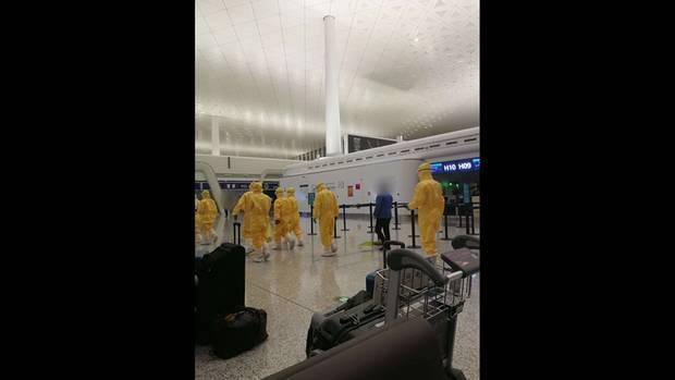 Mitarbeiter in Sicherheitsanzügen am Flughafen von Wuhan