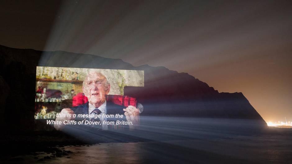 Bei Nacht sind nur die Konturen der Klippen von Dover zu sehen. Darauf die Projektion eines alten Mannes im Anzug