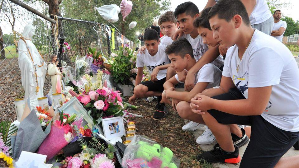 Mitschüler eines der von einem betrunkenen Autofahrer getöteten Jungen trauern am Unglücksort