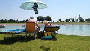 Senioren auf Sonnenliegen mit Sonnenschirm