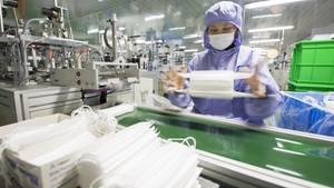 Eine Arbeiterin überprüft Atemschutzmasken in einer Fabrik im Osten Chinas